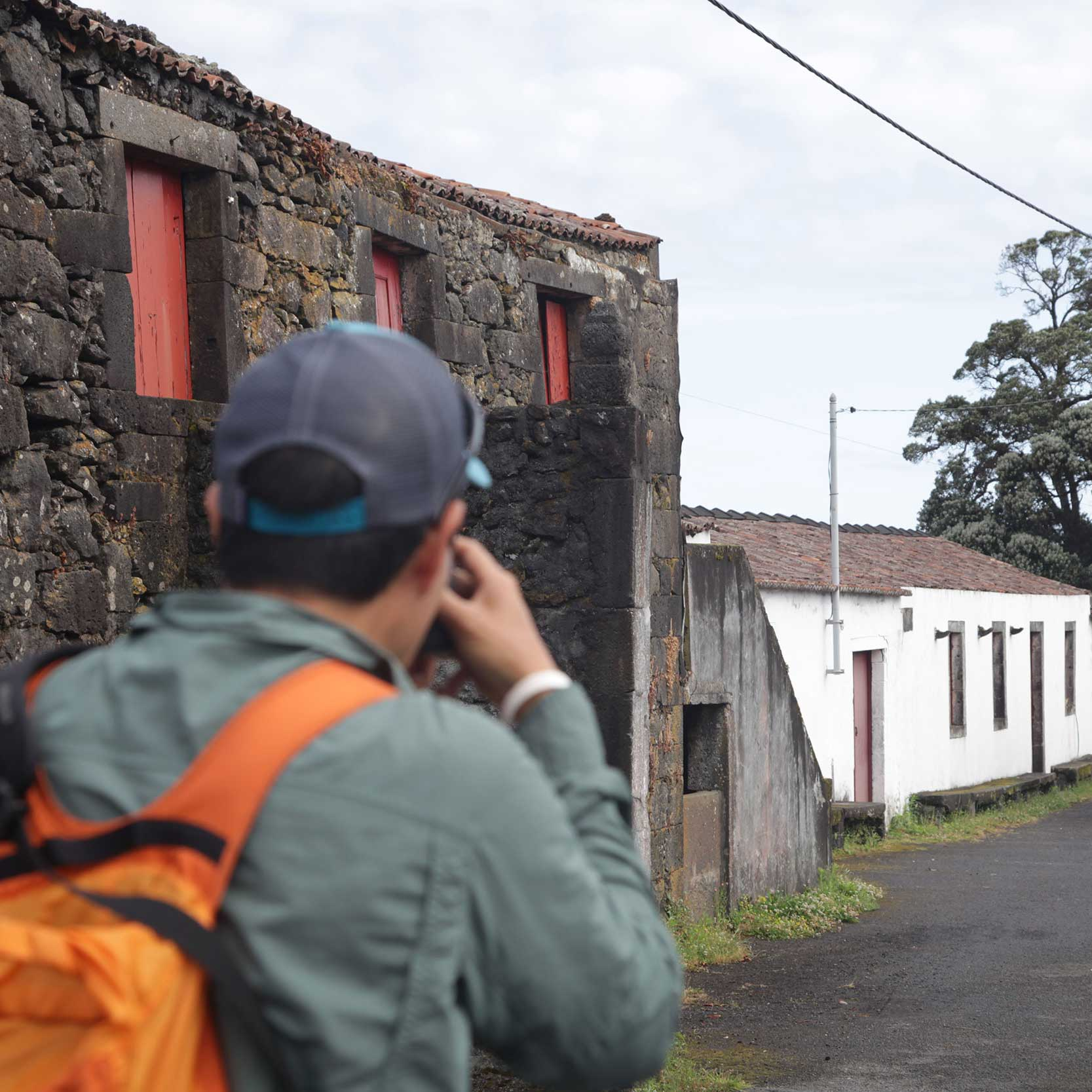 Customer photographing an old traditional architecture house. Faial half day includes the main attractions
