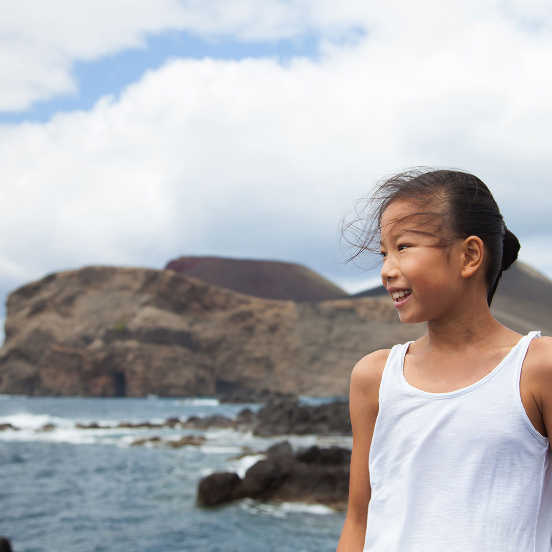 Girl with Capelinhos Volcano on the Background. Faial half day includes the main attractions.